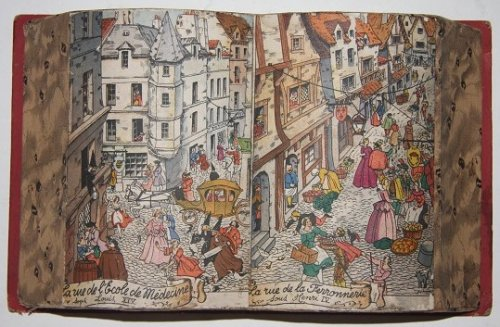 Faux Book Candy Box in the shape of an open book with a colorful Parisian street scene depicted on its two open pages La rue de lEcole de Medicine sous Louis XIV. La rue de la Ferronnerie sous Henry IV